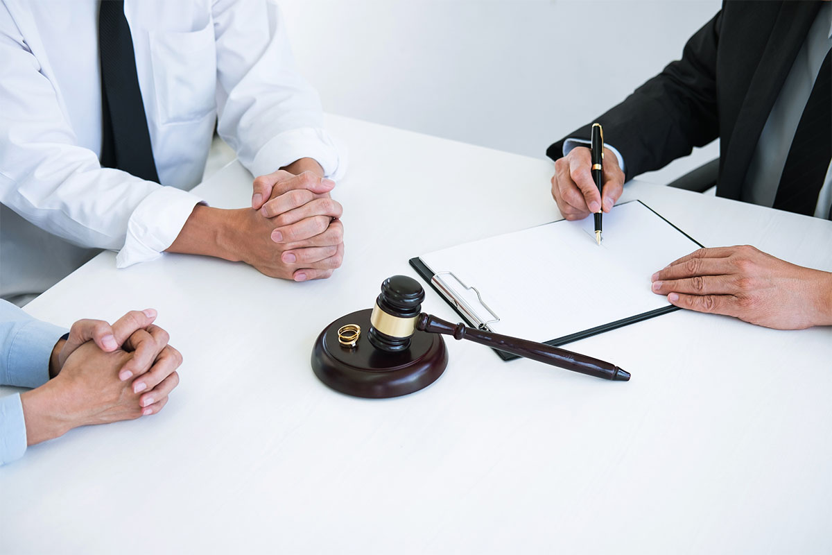 A gavel next to two wedding rings next to three people